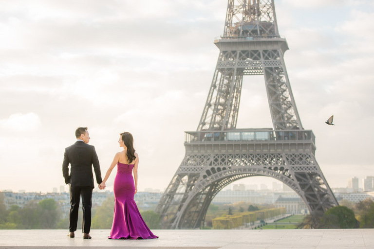 Couple walking in front of the Eiffel Tower during the engagement photoshoot