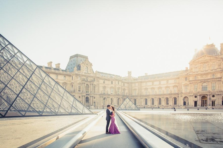 Couple at Louvre pyramid for their engagement photo session in Paris