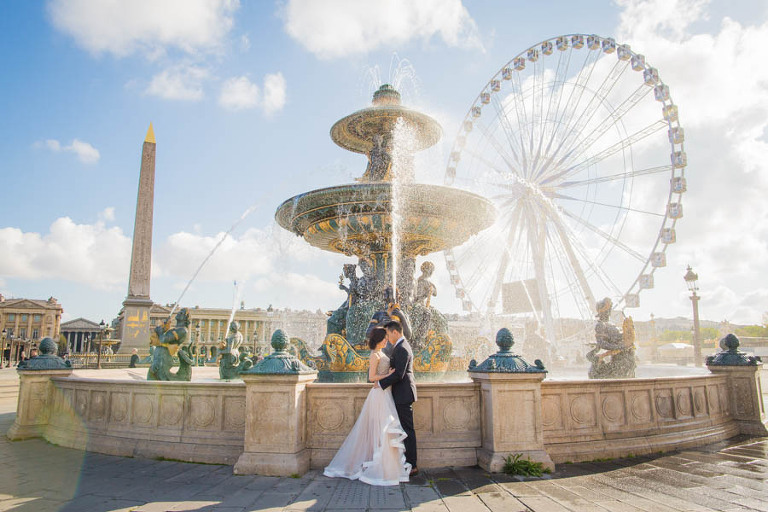 Engagement photo in Paris of couple in front of a fountain at Concorde square